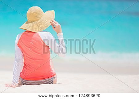 back view of woman in rashguard and sunhat enjoying picture perfect caribbean beach with turquoise water vacation and sun protection concept copyspace on the right