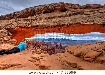 Woman looking at view of canyon and La Sal Mountains from Mesa Arch in Canyonlands National Park. Moab. Utah. United States.