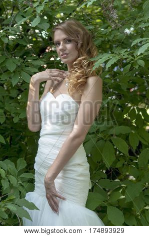 Beautiful tall slim red-haired girl in a bride's dress