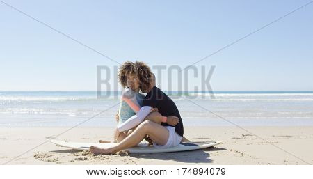 A couple embracing on a surfboard