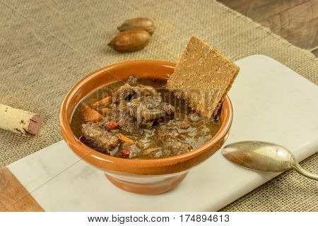 Meat and vegetable stew in an earthenware bowl, with a flatbread and a wine cork