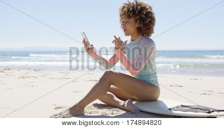 Smiling female on beach using smartphone