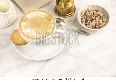 A cup of coffee with milk with a butter cookie and a milk jar on a white marble table, with a place for text. Selective focus