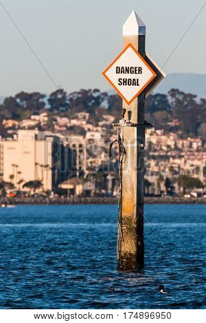 A shoal boating warning sign in a harbor.