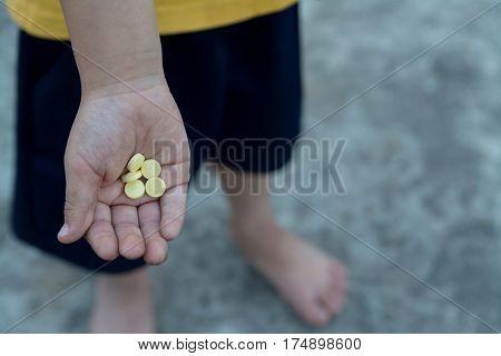 yellow round pill vitamin in dirty children hand
