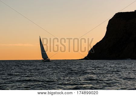Point Loma peninsula with a nearby sailboat at dusk in San Diego, California.