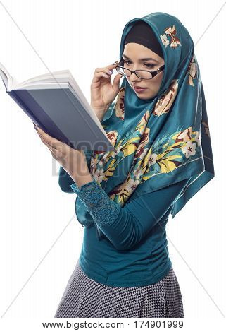 Female foreign exchange student wearing glasses and a hijab reading a text book. The conservative outfit is associated with muslims or middle eastern and east european culture.