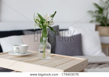 Bedroom grey interior with small table on bed with mug of coffee on it.