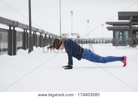 Sport girl model doing pushups during work out fitness at snow winter outdoor, telephoto