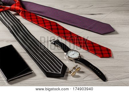 Color silk neckties watch with a leather strap cufflinks sell phone on a gray wooden background