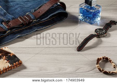 Man perfume watch with a leather strap jeans with leather belt amulet and leather purse on a gray wooden background