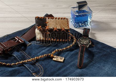 Man perfume watch with a leather strap jeans with leather belt leather purse and amulet on a gray wooden background