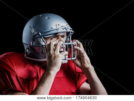 Aggressive american football player holding his helmet against black background