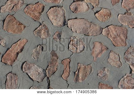Pinkish rocks inlaid in cement, with lines incised around them, to form a path or patio surface in Mexico.