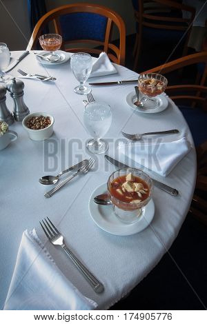 Round table with white cloth set for dinner in Ecuador, with glass cups of cevichi served as appetizer, with popcorn and corn nuts.
