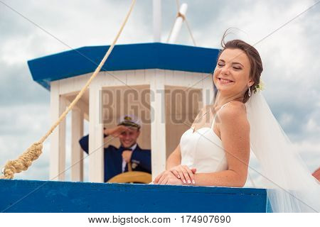 Wedding couple on small boat. The bride and groom on the ship.