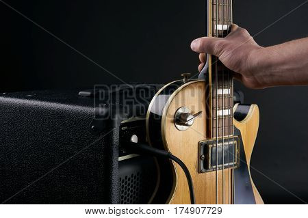 Hand puts vintage wooden electric bass guitar to combo amplifier on the black background