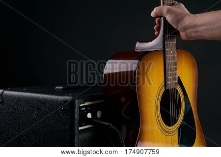 Hand puts acoustic classical guitar to combo amplifier on the black background
