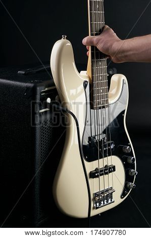 Hand puts black and white electric bass guitar to combo amplifier on the black background