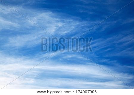 White spindrift clouds on blue sky background