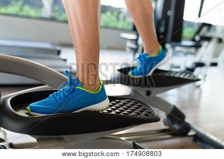 Woman doing exercises in the gym on elliptical cross trainer