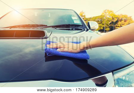 Asian woman's hand wiping surface of car by micro fiber cloth. poster