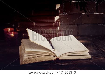 Old vintage books laying like a tower on a dark wooden table and one open book. Red hard cover burning candle flames.