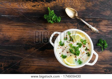 Avgolemono, Chicken Soup With Egg-lemon Sauce, Rice And Fresh Parsley Leaves In White Bowl On Wooden
