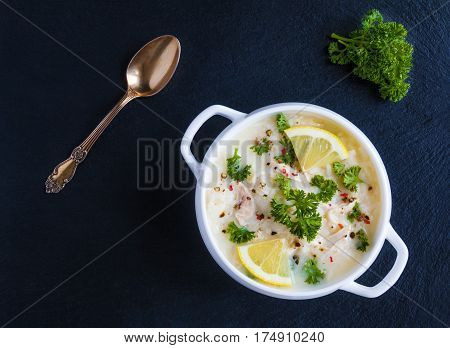 Avgolemono chicken soup with egg-lemon sauce rice and fresh parsley leaves in white bowl on black stone background. Top view.