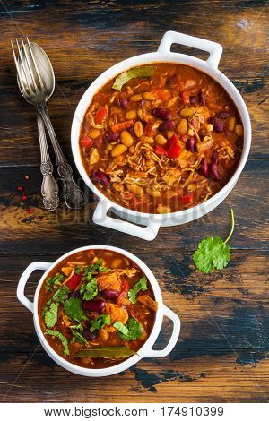 Turkey Chili in white bowl and casserole on wooden table top view. Stewed with beans tomatoes bell pepper onion garlic thyme cinnamon chocolate and fresh cilantro.