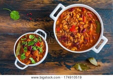 Turkey chili stewed with beans tomatoes bell pepper onion garlic thyme cinnamon chocolate and fresh cilantro in white bowl and casserole on wooden table.