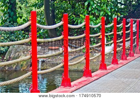 pedestrian bridge built in art wooden red railing and hemp ropes in the park of Pinocchio in Italy