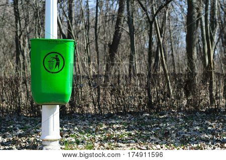 Green garbage can on white pole in park - spring time - midday