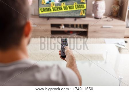 Man with remote control watching crime serie in TV at home