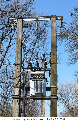 High voltage Power Transformer mounted on two concrete poles in forest - spring time