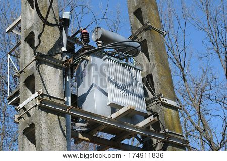 detail of High voltage Power Transformer mounted on two concrete poles in forest - spring time