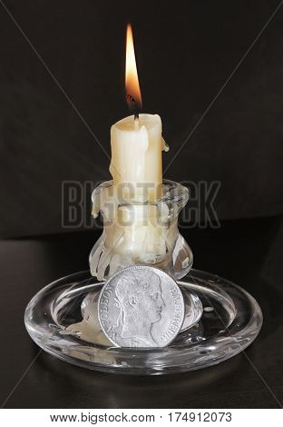 Close up view of old fashioned glass candlestick with a burning candle and vintage French 5 Francs silver coin with Napoleon Bonaparte portrait.