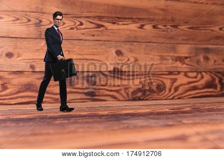 young business man with briefcase walking on old wood background