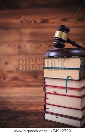 stack of law books with judge's gavel on top , studio picture on old wood background
