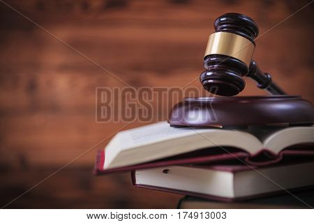judge's gavel on top of pile of law books , studio picture on wooden background