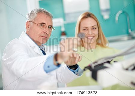 Male dentist looking patient's snapshot of teeth in dental practice