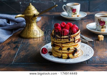 Stack of homemade pancakes with raspberries and chocolate vintage white plate Turkish coffee pot forks cups brown sugar wooden table.