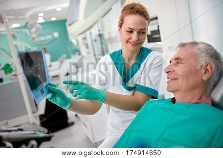 Nice female dentist showing dental X-ray to male patient