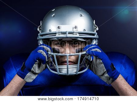 American football player adjusting his helmet against blue background