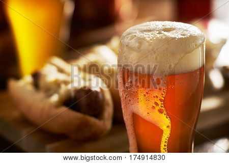 IPA beer with overflowing foamy head in mug served with bratwursts