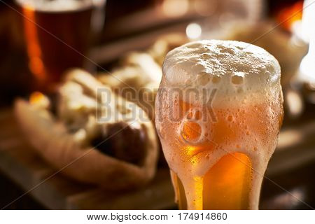 amber beer with overflowing foamy head and bratwursts in background