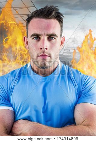 Digital composition of athlete standing with his arms crossed against fire in background