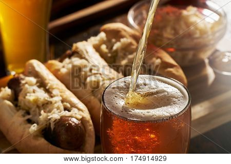pouring beer into mug with bratwursts in background