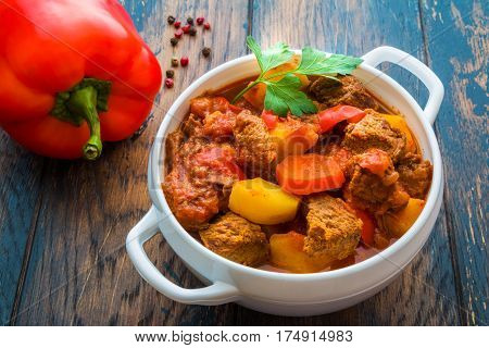 Traditional Hungarian dish goulash slow-cooked with beef potatoes carrot tomatoes paprika onion and bell peppers. White bowl on wooden table.