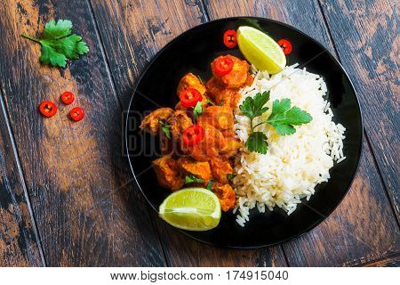 Traditional Indian cuisine chicken curry with fresh chilli pepper lime and parsley and boiled rice on a black ceramic plate on the wooden table top view.